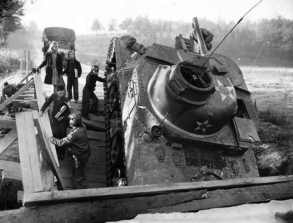 2nd_Armored_Division_Troops_Help_Children_Past_Crashed_M3_lee