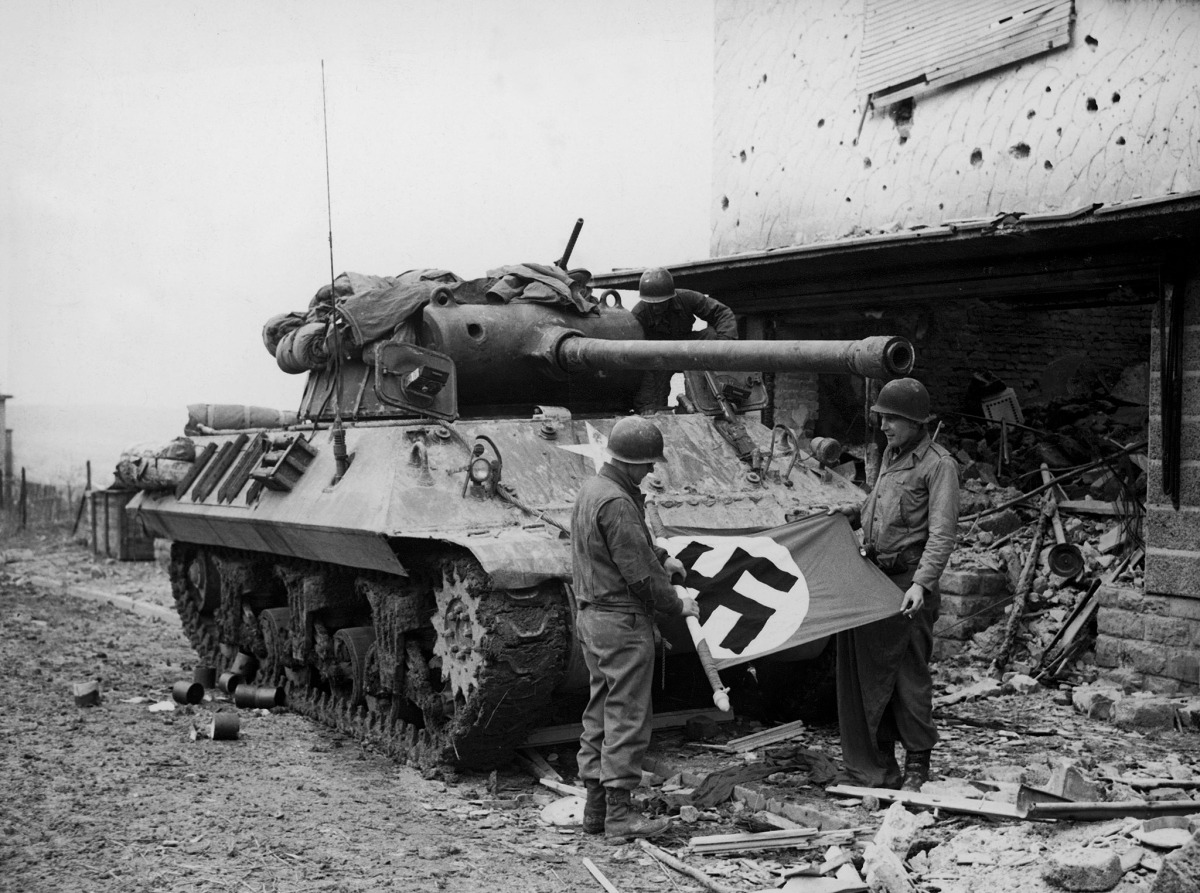American soldiers of Patton's Third Army standing in front of their M36 TD while rolling up a Nazi flag they have taken as a trophy after the capture of Bitberg.