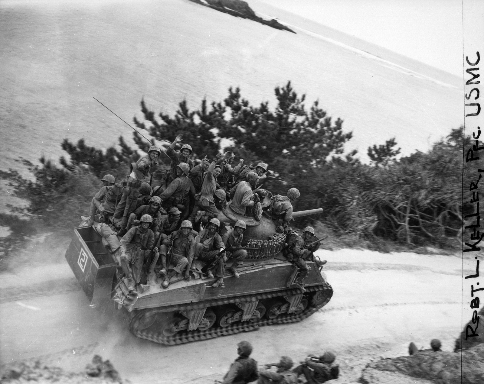 Riflemen of the 29th Marine Regiment ride a M4A3 Sherman 105mm of Company A, 6th Tank Battalion during the 6th Marine Division's drive on Chuda along the west coast of Okinawa. After expecting a contested landing on April 1, 1945, and seeing little of the Japanese, the Americans were in high spirits as objectives are taken ahead of schedule in Northern Okinawa; the Shuri Line would rob them of their high morale. The 29th Marines cut off the Motobu Peninsula and seized Chuda at 1200 Hours on April 6, 1945. Tank-infantry teams encountered sporadic resistance during the initial invasion; most problems were from the Japanese blowing bridges as they retreated inland. Destruction of bridges had been inept; frequently only a span of the bridge had been blown or cracked. The engineers cut quick bypasses for the vehicles, repairing the broken spans later. 500 M4A3 Shermans with the M4 105mm gun were built in late 1944. Later versions of the 105mm Sherman had a more advanced horizontal volute spring suspension (HVSS) with wider tracks that allowed for a smoother ride. Note partially dismantled deep wading gear to allow the M4A3 to move through deep water during the landings a few days before. The M4A3 Sherman with the M4 105mm howitzer was not popular with the tankers, who preferred the M1 76mm high-velocity gun in case of tank-against-tank engagements. However, the 105mm-equipped Shermans were very popular with ground troops, who used tanks as mobile pillboxes, taking out Japanese positions with point-blank high explosive fire.